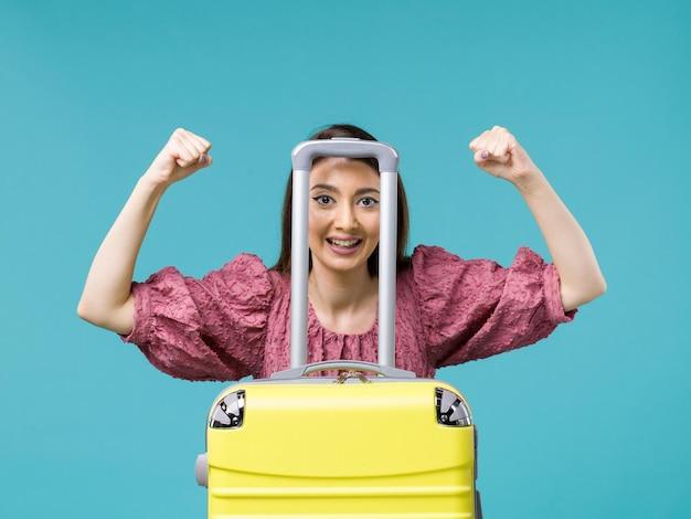 Mulher de férias vista frontal com sua grande bolsa amarela na mesa azul viagem verão viagem mulher mar humano