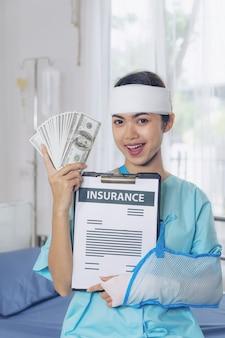 Mulher de ferimento de pacientes de acidente em cadeira de rodas no hospital, segurando-nos notas de dólar se sentir feliz de obter dinheiro do seguro do conceito médico de companhias de seguros