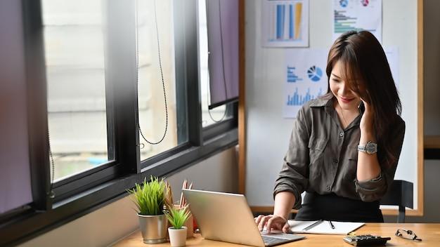 Mulher de finanças jovem chamando no telefone e usando o computador portátil.