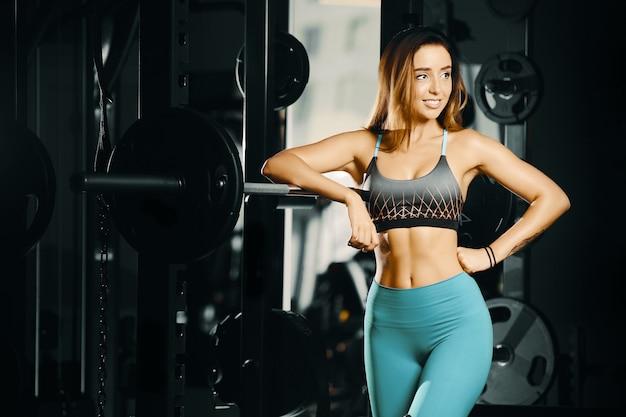 Mulher de fitness bombeamento músculos treino no ginásio