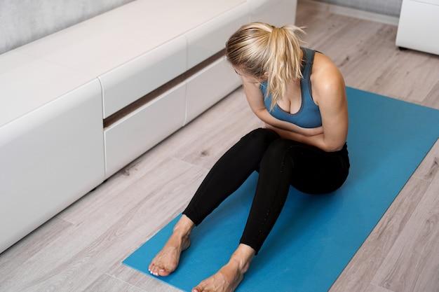 Mulher de fitness com dor de estômago durante o treino em casa. mulher infeliz sentada no tapete de ioga, sentindo dores