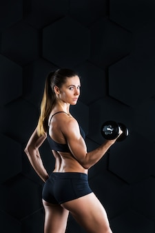 Mulher de fitness com halteres fazendo um exercício no escuro