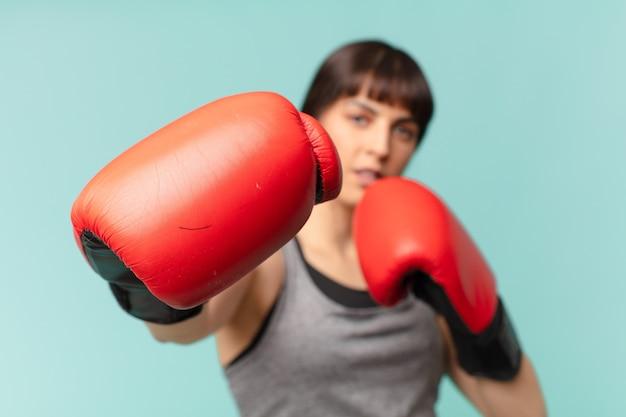 Mulher de fitness com luvas de boxe vermelhas.