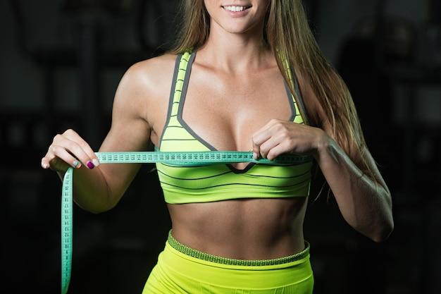 Mulher de fitness com roleta mede a circunferência do tórax close-up