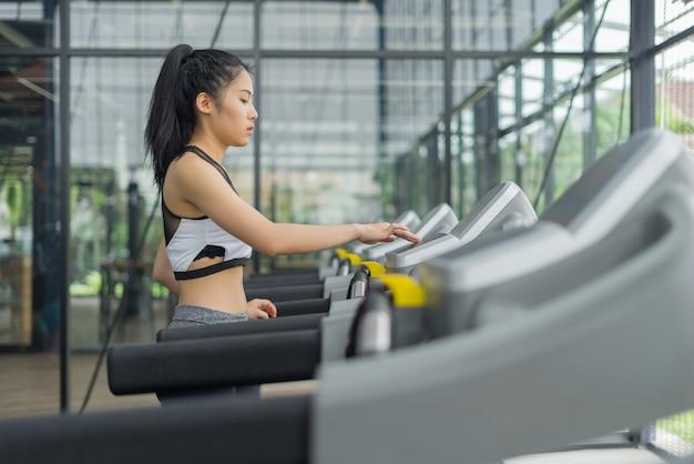 Mulher de fitness correndo com a máquina de exercício no ginásio