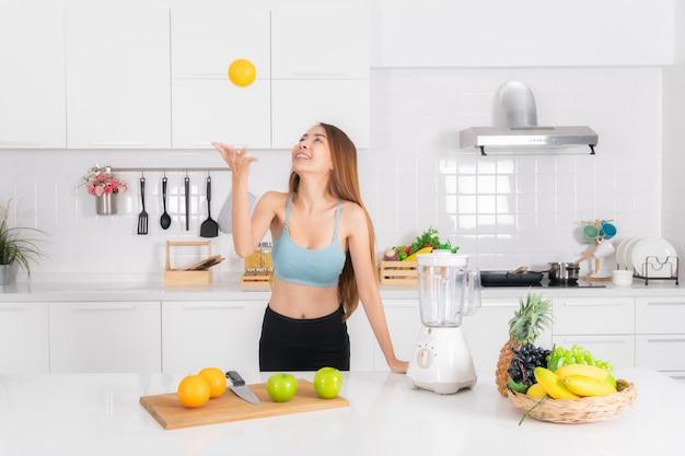 Mulher de fitness cozinhar suco batido na cozinha.