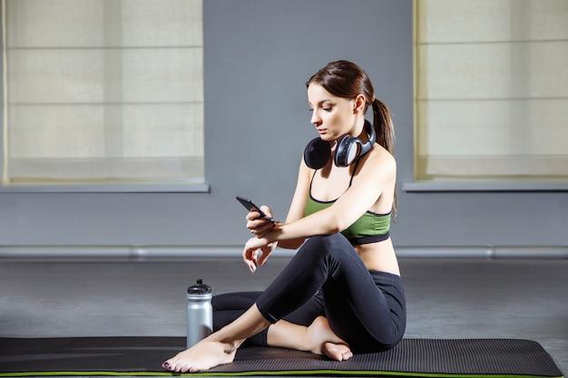 Mulher de fitness descansando depois de treino no ginásio