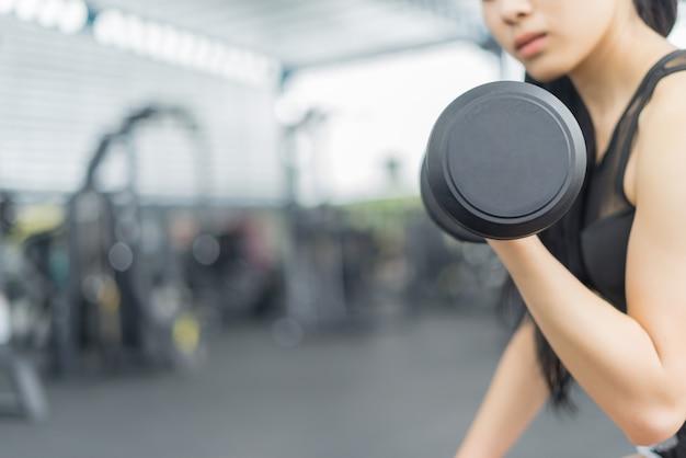 Mulher de fitness em treinamento mostrando exercícios com halteres no ginásio