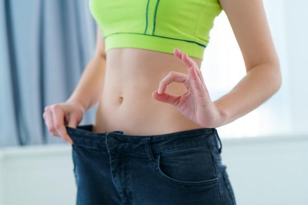 Mulher de fitness esporte saudável com cintura fina, puxando seus jeans grandes e mostrando a perda de resultados de peso. realização de objetivos, motivação e progresso em emagrecimento e dieta