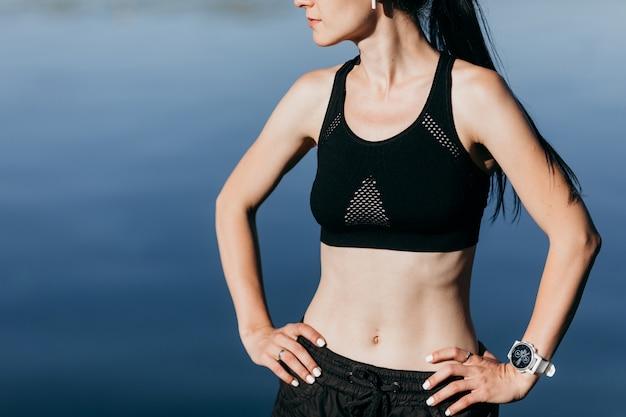 Mulher de fitness esportes jovens tem um descanso na praia ao ar livre, ouvir música com fones de ouvido.