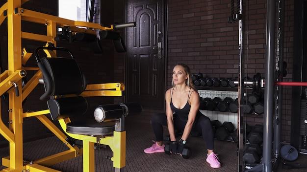 Mulher de fitness fazendo dead lift com halteres no ginásio