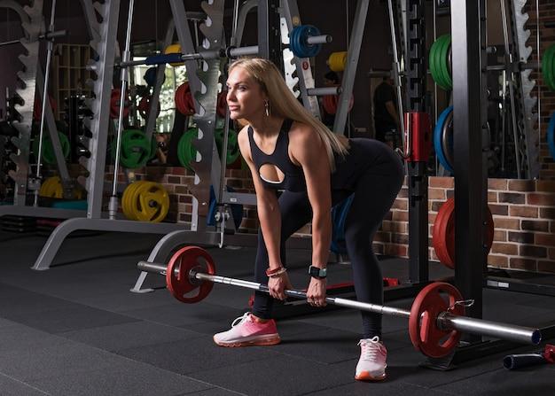 Mulher de fitness, fazendo exercício deadlift no ginásio