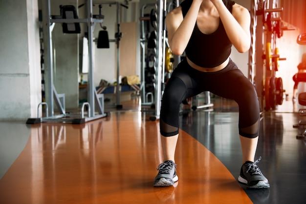 Mulher de fitness, fazendo exercícios de agachamento para queima de gordura e força de pernas no ginásio de esporte fitness