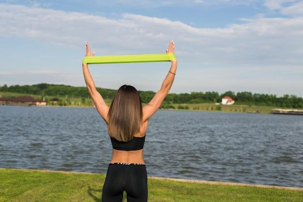 Mulher de fitness fazendo exercícios de treinamento ao ar livre no parque de verão. estilo de vida saudável do esporte do conceito.