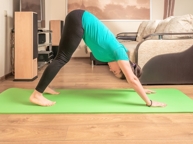 Mulher de fitness ioga alongamento fazendo prática de manhã no colchonete em casa.