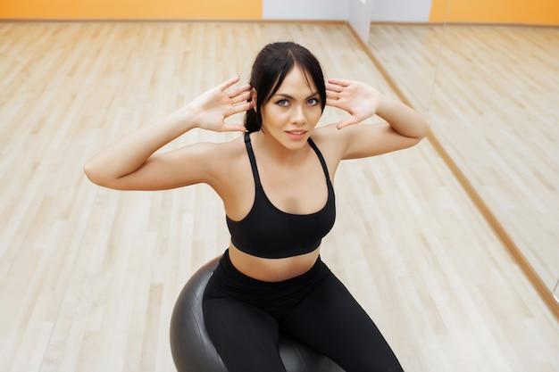Mulher de fitness. jovem mulher atraente fazendo exercícios usando bola