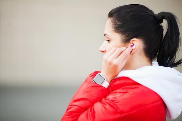 Mulher de fitness. jovem senhora no sportswear com fones de ouvido perto de um aeroporto