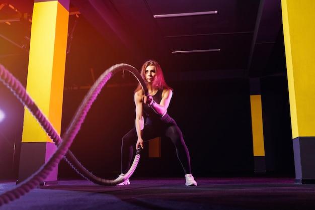 Mulher de fitness usando cordas de treinamento para exercício no ginásio. atleta malhando com cordas de batalha no ginásio cross.