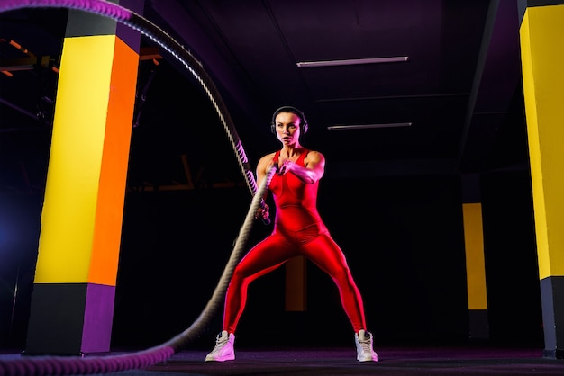 Mulher de fitness usando cordas de treinamento para exercício no ginásio. atleta malhando com cordas de batalha no ginásio.