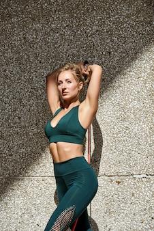 Mulher de fitness usando kettlebells fora durante o treinamento de força de aptidão contra copyspace