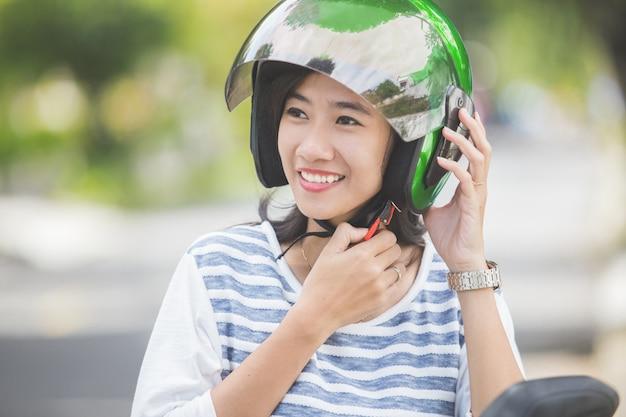Mulher de fixação do capacete de moto