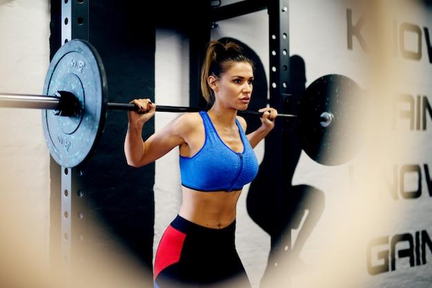 Mulher de forma atraente exercer com uma barra no ginásio moderno.