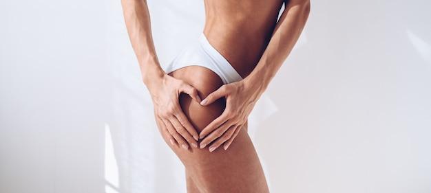 Mulher de forma irreconhecível em lingerie branca na parede branca isolada. mulher atraente magro muscular com barriga lisa. copie o espaço para texto. cuidados com o corpo, vida saudável e esportiva, conceito de remoção de pêlos