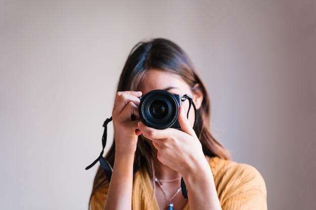 Mulher de fotógrafo em casa usando uma câmera reflex