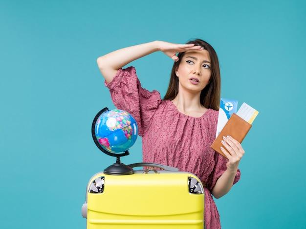 Mulher de frente para a viagem segurando a carteira com os ingressos no fundo azul mulher viagem férias viagem pelo mar viagem
