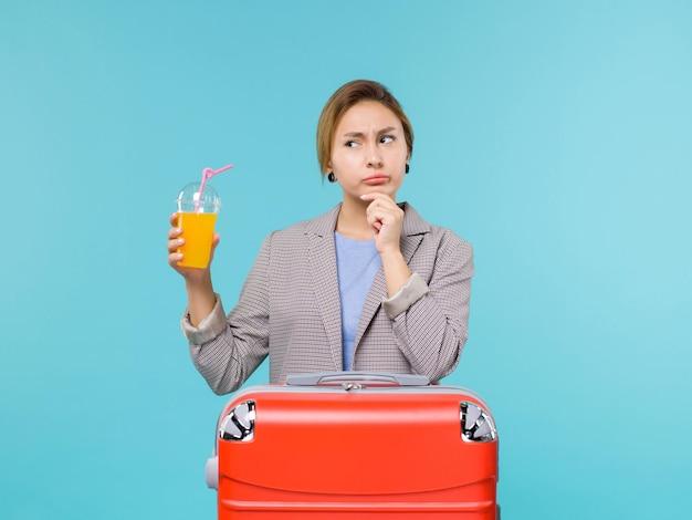 Mulher de frente para as férias com sua bolsa vermelha segurando suco fresco no fundo azul claro avião de férias viagem viagem marítima