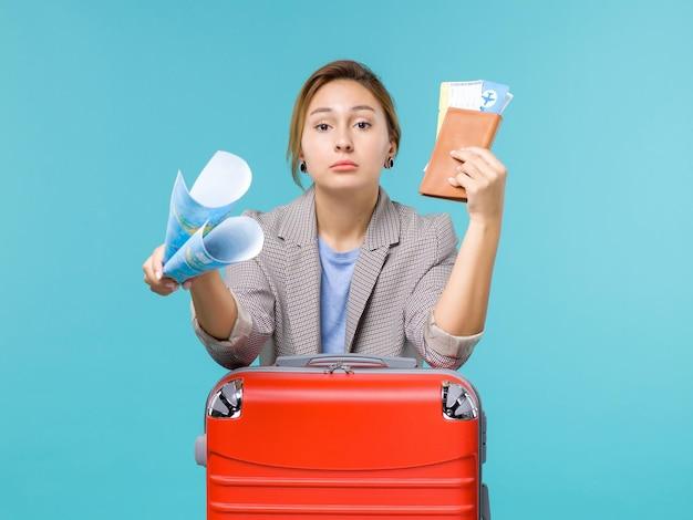 Mulher de frente para as férias segurando a carteira do mapa e os ingressos no plano de fundo azul claro avião viagem viagem viagem férias