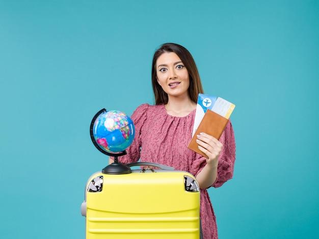 Mulher de frente para as férias segurando a carteira e a passagem no piso azul