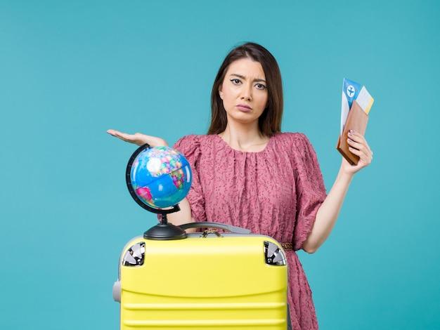 Mulher de frente para as férias segurando a carteira e o bilhete em um fundo azul claro viagem ao mar férias mulher viagem viagem