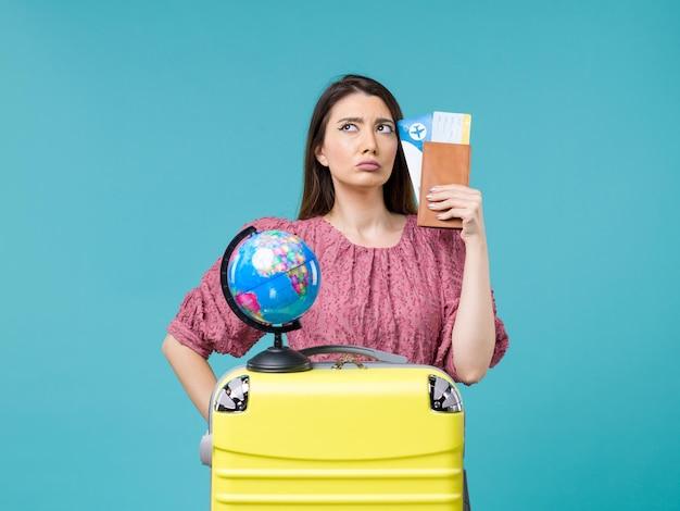 Mulher de frente para as férias segurando a carteira e o bilhete no fundo azul viagem ao mar férias mulher viagem viagem