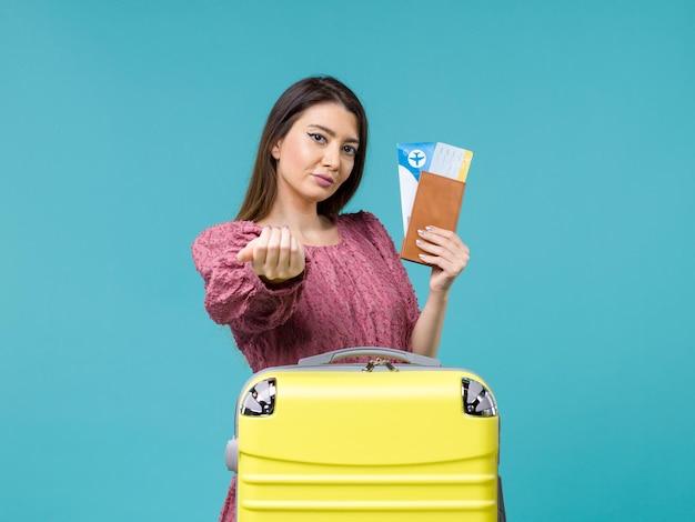 Mulher de frente para as férias segurando a carteira e os bilhetes chamando alguém no fundo azul, viagem, viagem, mulher, verão, mar, férias
