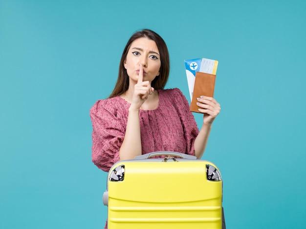 Mulher de frente para as férias, segurando a carteira e os ingressos em um fundo azul claro, viagem, mulher, verão, mar, férias