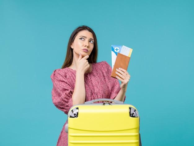 Mulher de frente para as férias segurando a carteira e os ingressos no fundo azul, viagem, viagem, férias, mulher, verão, mar