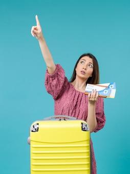Mulher de frente para as férias segurando a carteira e os ingressos no fundo azul.