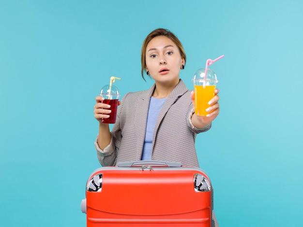 Mulher de frente para as férias segurando bebidas frescas na mesa azul viagem viagem férias viagem hidroavião
