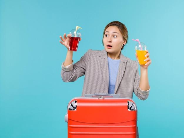 Mulher de frente para as férias, segurando bebidas frescas no fundo azul claro, viagem do mar, férias, avião, viagem, viagem