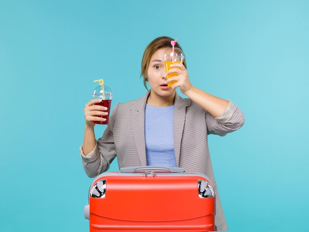 Mulher de frente para as férias, segurando bebidas frescas no fundo azul, viagem ao mar, férias, avião, viagem, viagem