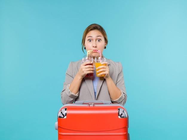 Mulher de frente para as férias segurando bebidas frescas no fundo azul.