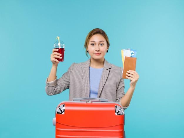 Mulher de frente para as férias segurando suco de cereja fresco e bilhetes na mesa azul claro viagem viagem avião viagem de férias