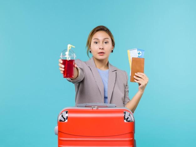 Mulher de frente para as férias segurando suco de cereja fresco e ingressos no fundo azul viagem viagem avião viagem de férias
