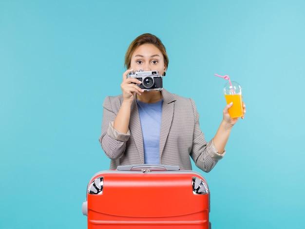 Mulher de frente para as férias segurando suco fresco e câmera na mesa azul claro mar férias viagem viagem viagem
