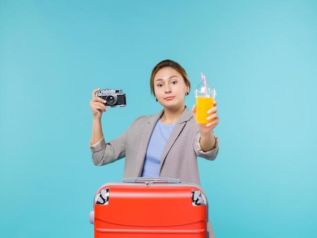 Mulher de frente para as férias segurando suco fresco e câmera na viagem de viagem de viagem de férias de fundo azul claro