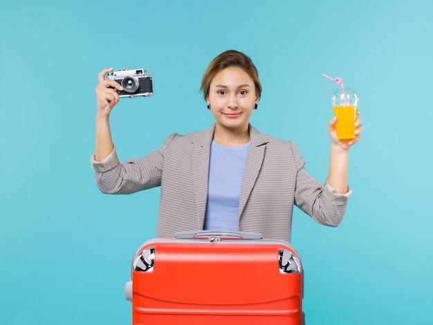 Mulher de frente para as férias segurando suco fresco e câmera no fundo azul mar férias viagem viagem viagem