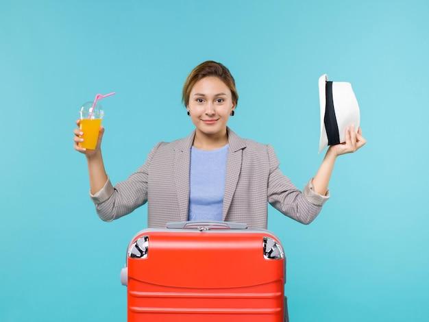 Mulher de frente para as férias segurando suco fresco e chapéu sorrindo no fundo azul mar férias viagem viagem viagem