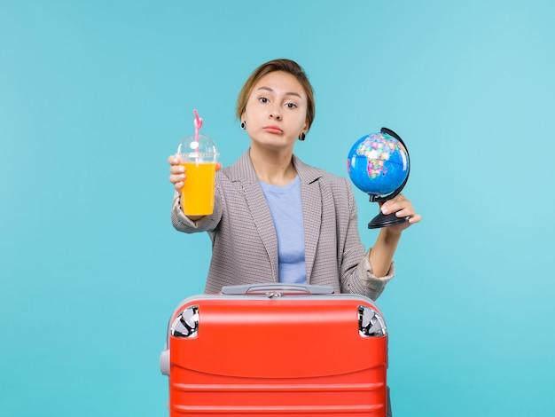 Mulher de frente para as férias segurando suco fresco e globo sobre fundo azul claro viagem ao mar viagem de férias