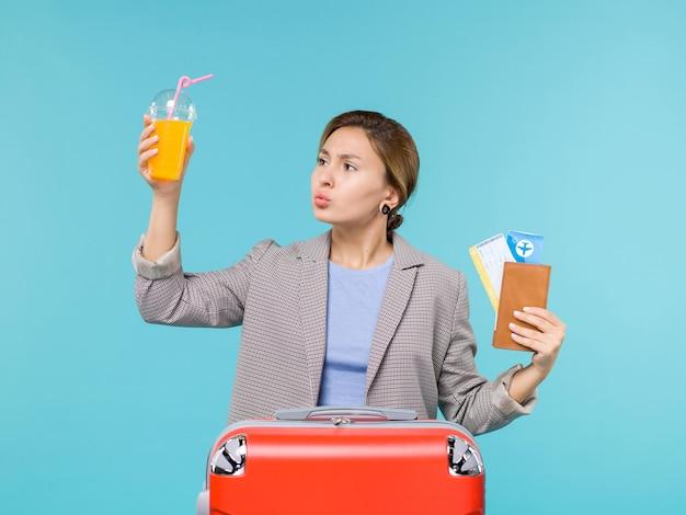 Mulher de frente para as férias segurando suco fresco e ingressos na mesa azul, mar, férias, avião, viagem, viagem, viagem